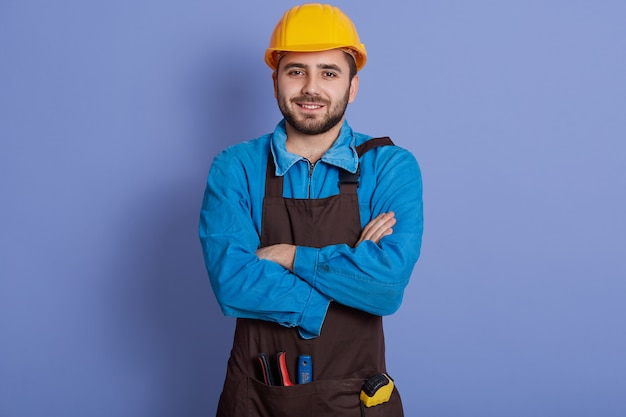 Positive repairman wears yellow protective construction helmet, shirt and brown apron, ready for house renovation.