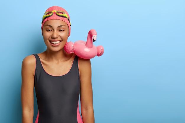 水泳の準備ができてポジティブな安らかな暗い肌の女性