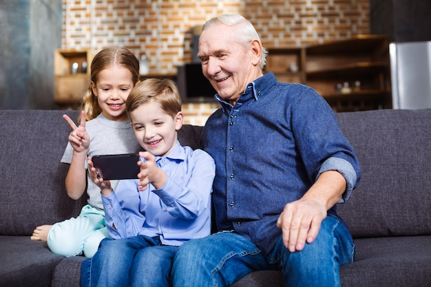 Positive retired man sitting on the couch while making selfies with his grandchildren