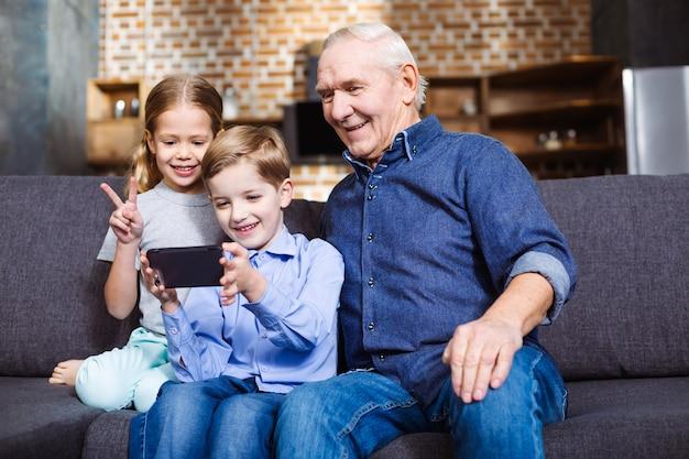Позитивный пенсионер сидит на диване, делая селфи со своими внуками