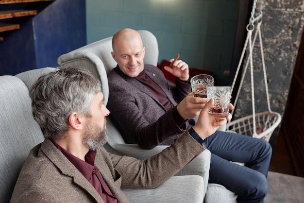 Позитивные богатые мужчины среднего возраста в стильных нарядах сидят в креслах и расслабляются с виски после рабочего дня
