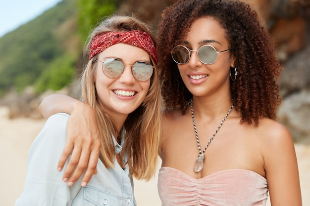 Positive romantic same sex couple spend summer holidays in resort country, have happy expressions and smiles, pose together on sandy beach. cuddling women being in love. lesbians recreate at hot city