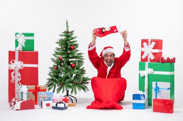 地面に座って、贈り物の近くで頭にクリスマスの靴下を上げ、白い背景に新年のツリーを飾ったポジティブなサンタクロース