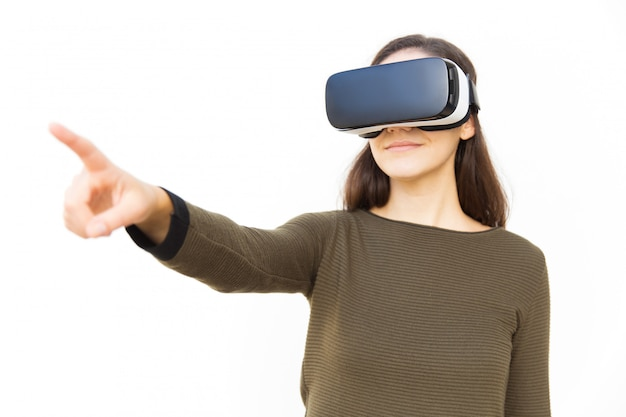 Positive satisfied woman in vr headset pointing finger away