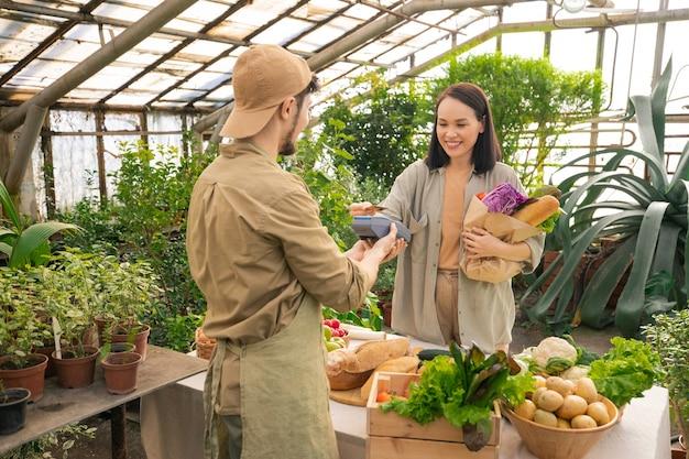 農家の市場で製品の支払いをしながら、ワイヤレスクレジットカードを使用したフルペーパーバッグで前向きに満足している若いアジアの顧客