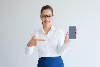 Positive satisfied young female manager pointing at gadget screen.