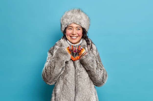 Positive scandinavian woman in winter outerwear makes heart gesture expresses love and care smiles joyfully has white teeth isolated over blue wall