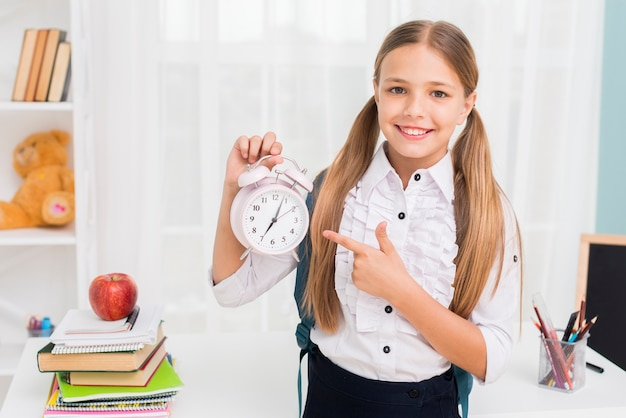 Positive schoolgirl pointing at clock