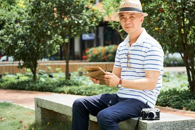 Позитивный старший азиатский мужчина в парке