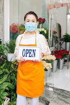 의료용 마스크를 쓴 긍정적인 아시아 여성이 손에 열린 사인을 들고 꽃가게에 서 있다