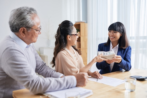 Positive senior couple giving money for down payment to real estate manager at meeting
