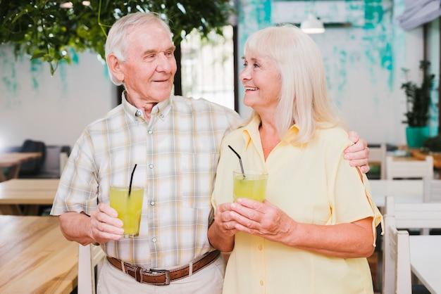 Positive senior couple hugging in cafe and enjoying refreshing drink