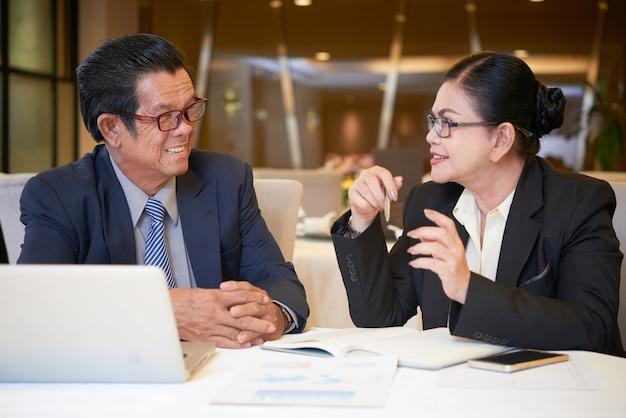 マーケティング計画を議論するためにレストランのテーブルで会う前向きな上級起業家