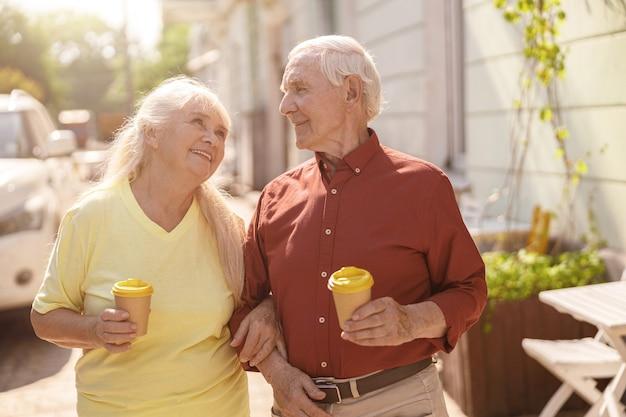 カップを持つポジティブなシニア家族のカップルが通りに沿って一緒に歩く