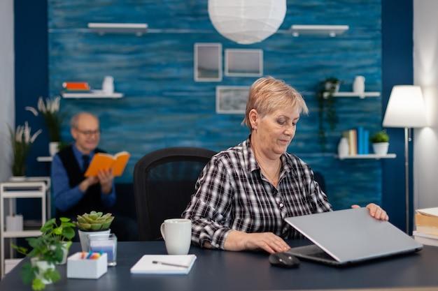 긍정적인 시니어 프리랜서가 홈 오피스에 앉아 노트북을 열고 책을 읽고 있는 성숙한 남편입니다. 집 거실에 있는 노인 여성은 실내 책상에 앉아 의사 소통을 위해 모더 테크놀로이를 사용합니다.