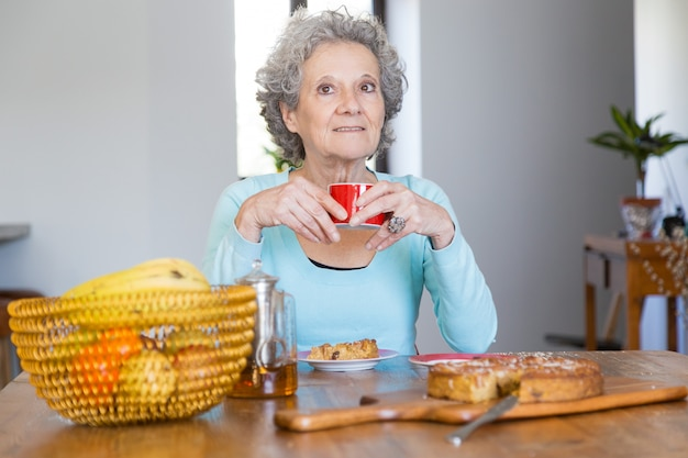 Positive senior lady enjoying tasty pie