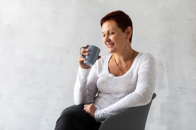 Positive senior lady holding a mug