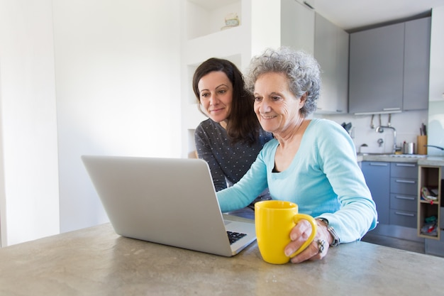Positive senior lady showing photos to daughter on laptop