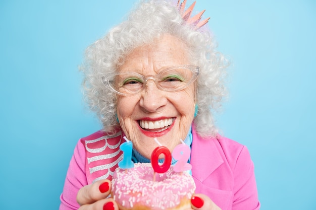 Positive senior lady smiles broadly has festive mood blows candles on doughnut makes wish on her 102nd birthday looks perfect has bright makeup wears styilish elegant clothes