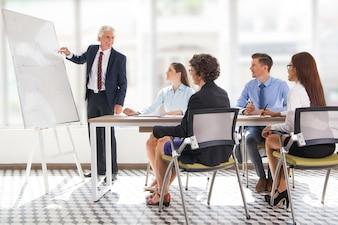 Positive senior leader drawing graph at meeting