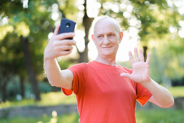 Positive senior man communicating online, showing hello in the park.
