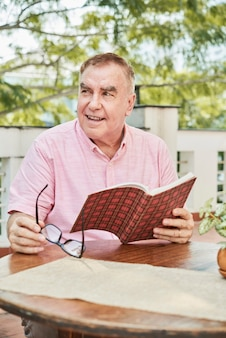 Positive senior man with book