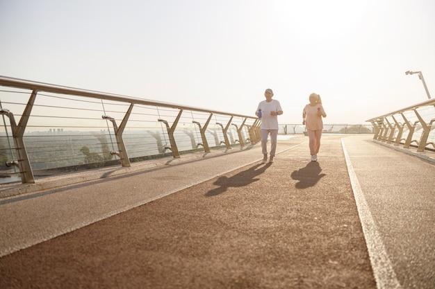 Позитивная старшая женщина и мужчина с бутылками бегают по мосту в летний вечер