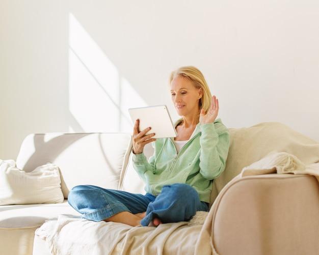 Позитивная старшая женщина, имеющая видеоконференцию по мобильному телефону с семьей, отдыхая на диване в