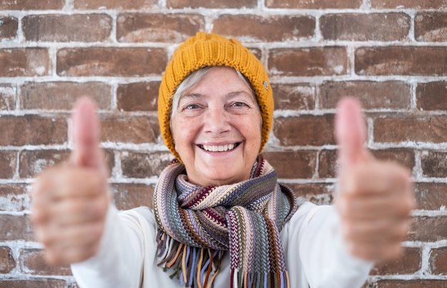 Positive senior woman with thumbs up smiling looking at camera - brick wall background