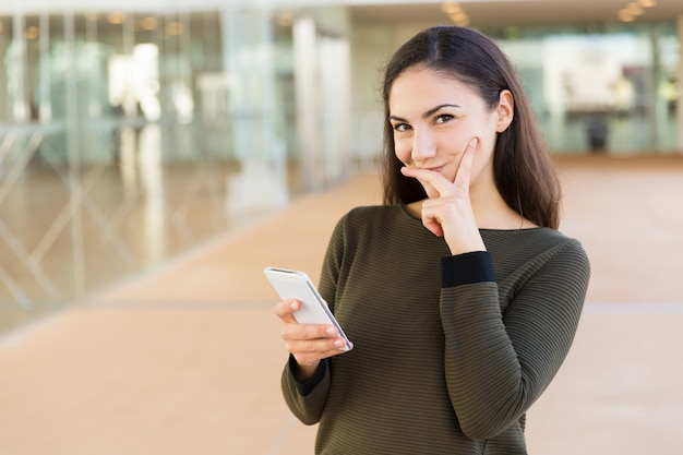 Positive shy latin woman with cellphone touching face