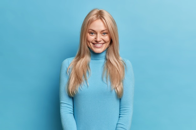 Positive shy woman with pleasant smile looks happy, dressed in casual turtleneck