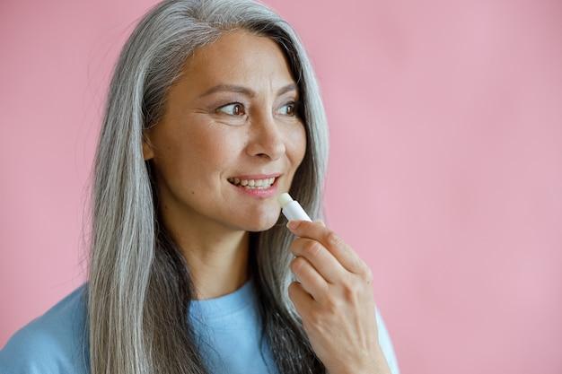 ポジティブな銀髪のアジアの女性はピンクの背景にリップクリームを適用します
