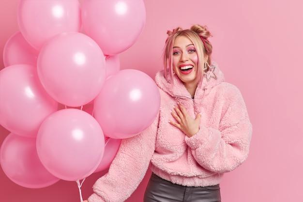 Позитивная искренняя женщина с двумя булочками улыбается, приятно празднует день рождения, держит кучу воздушных шаров, позирует на розовой стене, выражает счастливые чувства.