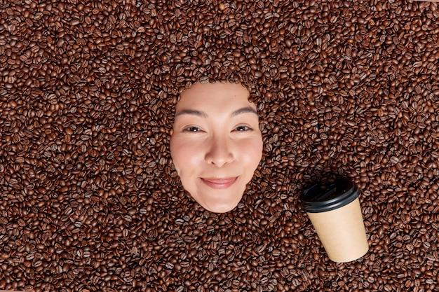 긍정적인 젊은 아시아 여성이 집에서 맛있는 커피 콩 요리법을 테스트하고 기분 좋은 향기 일회용 컵의 갈색 볶은 씨앗으로 덮인 카페인 음료를 준비합니다
