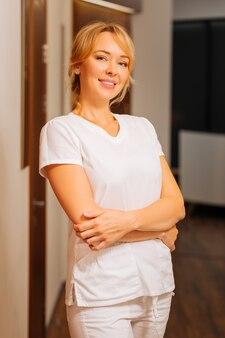직장에서 그녀의 유니폼을 입고 긍정적 인 숙련 된 미용사