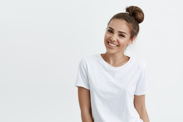 Positive slim european girl with bun hairstyle, smiling broadly while standing over white space, expressing confidence and sensuality.