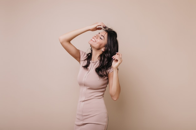 긍정적 인 날씬한 소녀는 그녀의 곱슬 검은 머리를 만집니다. 세련 된 드레스에 여자는 귀여운 미소