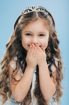 Positive small child covers mouth with hands, giggles positively, wears crown