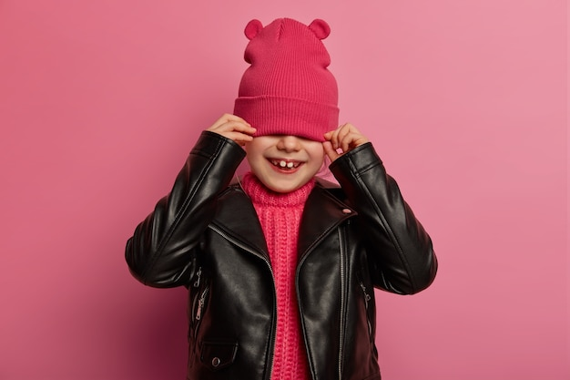 Positive small child hides face with pink hat, covers eyes, wears leather jacket, has playful happy smile, poses against rosy wall, feels upbeat, tries on fashionable outfit. children concept