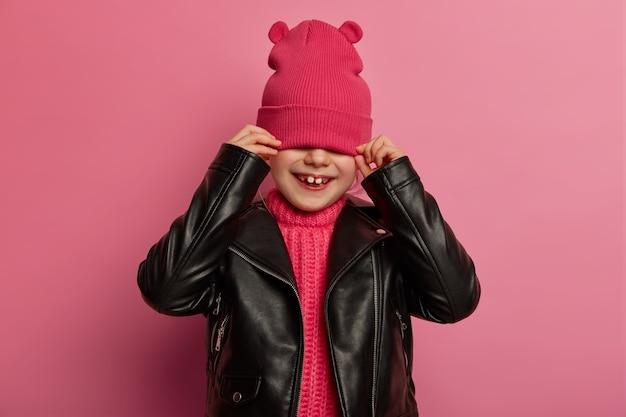 ポジティブな小さな子供はピンクの帽子で顔を隠し、目を覆い、革のジャケットを着て、遊び心のある幸せな笑顔を持ち、バラ色の壁に向かってポーズをとり、明るい気分で、ファッショナブルな服を着てみます。子供の概念
