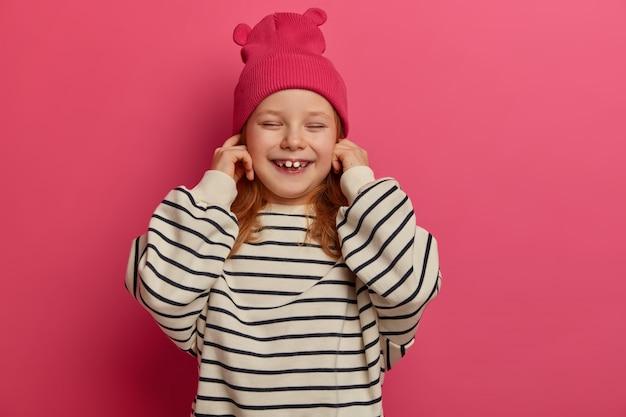 ポジティブな小さな子供は耳をふさぎ、大きな音を無視し、目を閉じて笑い、ピンクの帽子と特大の縞模様のジャンパーを着て、屋内でポーズをとります。いたずらな女の子、両親の声を聞きたくない