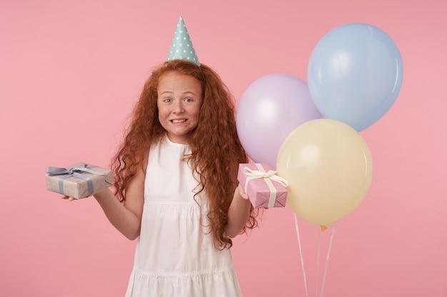 お祝いの服を着たポジティブな小さな子供は休日を祝い、ピンクの背景に立ち、元気です。プレゼントをもらえることにワクワクし、嬉しそうな笑顔でカメラを見る
