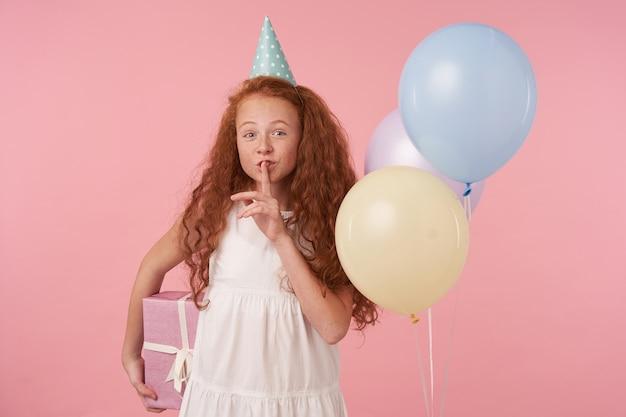Позитивный маленький рыжий ребенок празднует праздник на розовом фоне в белом платье и шапочке для дня рождения. держит подарочную коробку и поднимает руку ко рту в жесте молчания, собираясь сделать сюрприз