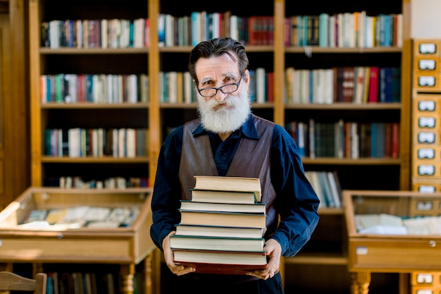 Positive smart old bearded man in dark shirt and leather vest, library worker, teacher, working in library, holding stack of books while standing over book shelves background