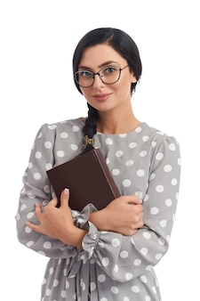 Positive smart woman with dark haired tied in pigtail posing on camera with book in hands.