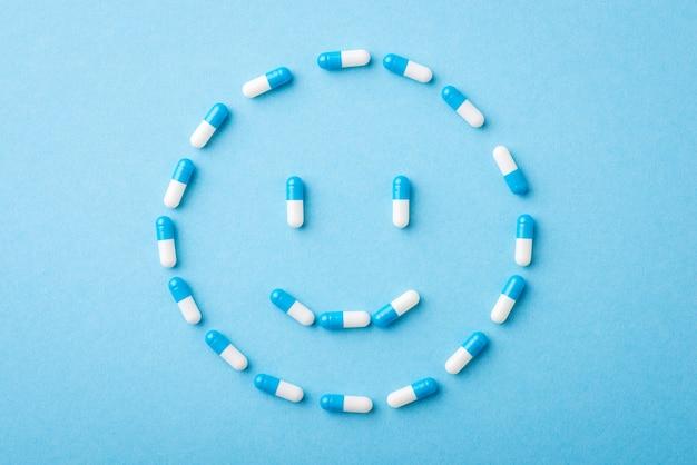 青い背景の上の丸薬で作られたポジティブな笑顔