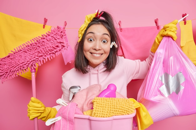 Positive smiling asian woman maid poses with garbage bag and mop poses near basin of laundry wears protective rubber gloves ready for spring