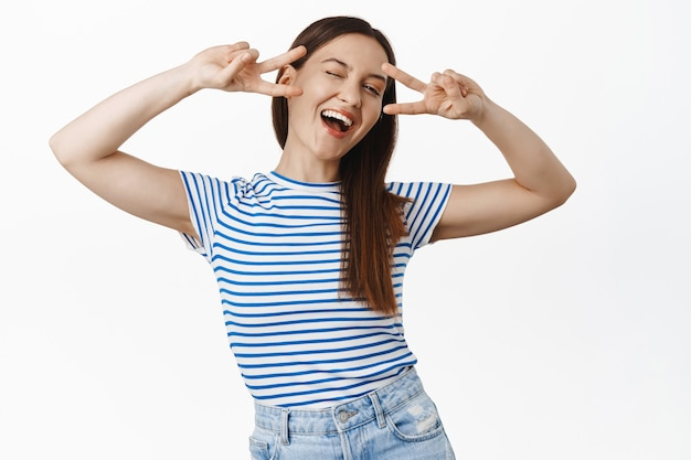 Positive smiling brunette woman shows peace v-sign, laughing, winking and looking carefree, positivity and joy, happy people concept, white wall.