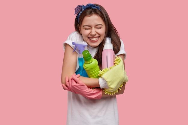 Позитивно улыбающаяся темноволосая женщина обнимает бутылки с моющими средствами и чистящими спреями, дезодорантом