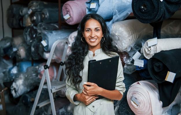 Положительный улыбающийся сотрудник с блокнотом находится в хранилище, полном ткани.